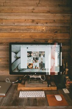 Loving the rustic look of the hardwood desk and wall against the modern, minimalist look of the computer.