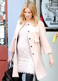 Sienna Miller wears thick black tights with a short white dress.