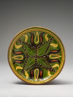 Plate  Attributed to Solomon Grimm (1787–1847)  Date: ca. 1815–25 Geography: Mid-Atlantic, Pennsylvania, United States Culture: American Medium: Earthenware; Redware with sgraffito and slip decoration