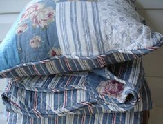 Clifton throw and cushion is a printed design in blue and white with thin red stripes on the back and Flowers