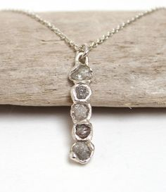 Rough diamond bar pendant on fine silver chain - TGRDN4 Hand crafted from sterling silver and set with 5 uncut, raw diamonds and given Tamaraa signature frosted finish.  Materials: Sterling silver and grey rough diamonds. Chain Length: 20 inches. Total weight of diamonds: 1.5ct Pendant size: Approx 2.2cm x 0.5cm  Please note that due to the unique nature of rough diamonds and the hand crafted techniques Tamara uses each piece may vary ever so slightly to the images shown.  Hand crafted by…
