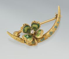 A gold, enamel and diamond brooch combining a crescent and a lucky four-leaf clover. (aspireauctions.com)