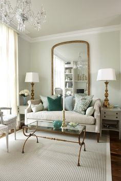 Light green walls paint color, floor length gold mirror, Sarah Richardson Nicole Sofa with green pillows, antique brass glass-top cocktail table, antique gold lamps and white end tables.    Para Paints Eyelet