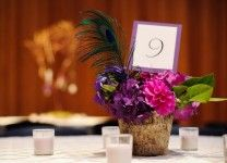 purple centerpieces with  peacock feather accent in birch container