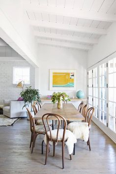In the dining space, a set of bentwood chairs surrounds a table made of locally salvaged pinewood | domino.com