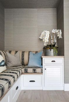Living room nook is clad in gray grasscloth wallpaper and filled with a L shaped built-in bench covered in taupe and black fabric.