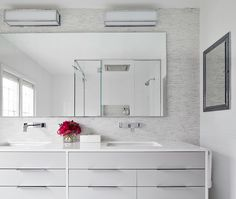 Sleek, contemporary bathroom with white dual vanity featuring gray drawer fronts below a white counter with his and her sinks pairing with wall mounted faucets. The vanity wall is tiled in white and grey linear mosaic tile which frames a simple vanity mirror highlighted by a pair of Restoration Hardware Pierce sconces alongside a inset mirrored medicine cabinet.