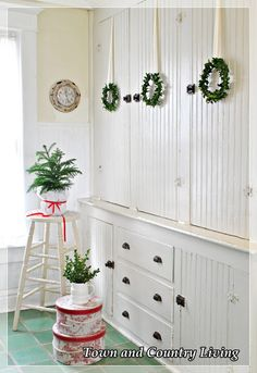 DIY Christmas Decor. How to make boxwood wreaths. A trio of wreaths are hung on a cabinet in a farmhouse kitchen.