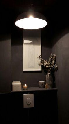 Toilet, muur bewerkt met betonverf.
