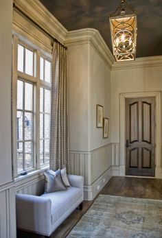 The deep gray ceiling in this foyer allows the extra-deep crown moldings to stand out by contrast. Given the high ceilings and the traditional style of the home, the choice to paint the ceiling and antique the moldings created a much warmer look than pure white would have.