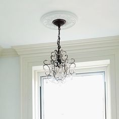 Bathroom fix up: Turn the ceiling into a focal point by installing a medallion and handsome hanging fixture, such as this bronze-toned light with crystal teardrops. If installed over a tub, as seen here, be sure there's at least 8 feet of clearance from the tub rim to the bottom of the pendant to comply with electrical code.