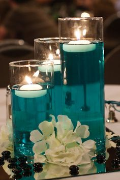 "A little bit of food color & water with some floating candles. Cylinders from dollar store. I like that we can bring in the ""tiffany blue"" color with the orange flowers and white candles"