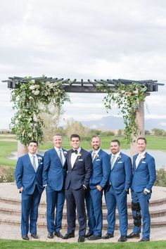 Encanterra Country Club Wedding in Phoenix, Arizona with cacti details and DIY getting-ready floral backdrop. Groom wore a classy black and navy tux and black bowtie while groomsmen wore slate blue suits. Photographed by Scottsdale wedding photographers Amy and Jordan Demos, designed by Sassy Soirees Country Groomsmen, Groom And Groomsmen Suits, Groomsmen Outfits, Groomsmen Poses, Groom Tux, Blue Suit Wedding, Wedding Suits, Tuxedo Wedding, Wedding Dresses