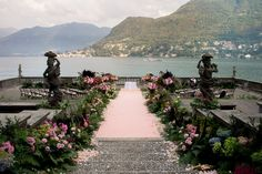 Organic wedding aisle decorations with flowers and pink carpet overlooking Lake Como