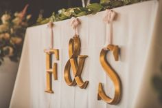 Metallic gold wedding reception decor idea - gold initials hanging at sweetheart table {Heather Wilkinson}