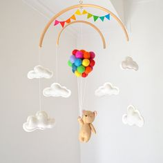 Neutral baby mobile featuring a little bear flying balloons, surrounded by clouds with a rainbow bunting banner  Hi! and thank you for visiting my shop! ❤ This adorable neutral gender baby mobile will capture everyones attention and would make the cutest addition to any nursery decor. ❤  The little bear is hand stitched by me. All items are handmade with 100% wool felt, bear and clouds are filled with hypo-allergenic polyester stuffing. The 27 multicolor balloons are sewn together and…
