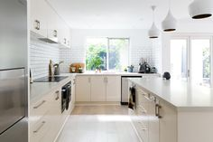Bright and spacious kitchen with a large kitchen island and beautiful white designer lamps. We love the bright wooden kitchen front and the large metal fridge! Click to find more inspiration!