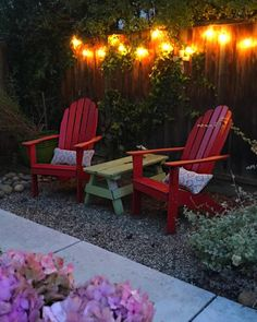 The+side+table+is+actually+a+vintage+painters'+bench,+which+is+low+enough+to+the+ground+to+work+with+the+low-slung+red+Adirondack+chairs.+California-based+DesignFix+also+used+recycled+rock+gravel+and+string+lights+when+designing+this+small+side+yard.
