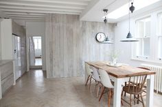 Driftwood like vertical paneling with open ceiling beams and lots of natural light.