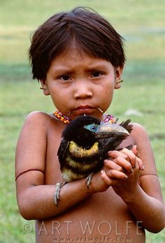 Yanomamo girl holds aracari in Parima Tapirapeco National Park (Venezuela) (© Art Wolfe/Art Wolfe Stock)