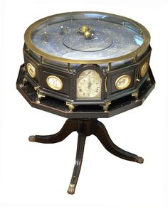 Grand Orrery - National Maritime Museum.  Grand orreries were educational tools and status symbols, affordable only to the most wealthy. This one stands on a polygonal black wooden base with four trestle legs and brass feet, surmounted by a shallow glass dome. Panels around the side of the base are gilt framed and painted with the twelve signs of the zodiac and, between Leo and Gemini, there is a clock signed by the maker (James Simmonds, London), which strikes on the hour.