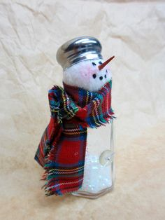 A glass salt shaker has been used to create his body, which a tiny bottle brush tree has been placed with artificial snow and some glitter. His head is made from fabric which has hand applied details. The scarf is made from a festive fabric with swirls in the background, golden