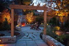Light and warmth. In addition to physical warmth, fireplaces add a dramatic light and a welcoming invitation to a space. In this garden, the visual warmth of the fireplace is enhanced by applying strategic lighting to the fiery leaves of the trees that flank its chimney. I would happily put on a sweater to enjoy the cozy warmth of this patio.