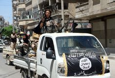 Fighters from Al-Qaeda's Syrian affiliate Al-Nusra Front drive in armed vehicles…