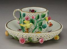 A 20th Century Meissen style schneeballen cabinet cup and saucer, encrusted with flowers and birds amongst gilt branches, underglaze blue crossed swords mark.