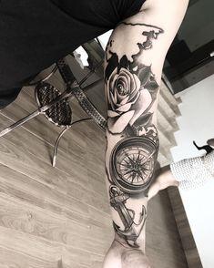 Tatuagem criada por Robinho Tattoo de Goiania, Goias. Rosa dos ventos, âncora e flores em preto e cinza.