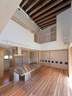 家の中央に配したキッチンは吹抜けで二階とも繋がる