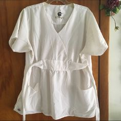 Dickies❤️White Scrub Top Size medium❤️Dickies scrub top❤️ties in back❤️side slits❤️two front pockets❤️worn a handful of times,like new❤️tadesbundle❤️please use offer button via all offers❤️thank you Tops Tees - Short Sleeve