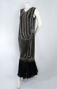 Deco beaded evening dress, late 1920s. The torso is decorated with alternating stripes of opaque white and clear crystal beads that swirl toward elaborate beaded medallions on one side. The scalloped hem border of the original flapper dress has a looped fringe of clear crystal beads.