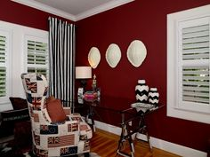 British charm infuses this red contemporary home office thanks to British flags adorning the comfy wingback used as a desk chair. Black-and-white Nate Berkus-designed chevron vases from Target tie in with the black-and-white-striped curtains.