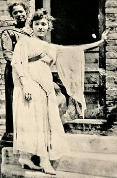 A Jerome, Arizona, harlot shows off her finery in this photograph that was probably taken in the red light district on Hull Avenue. Some have speculated she may have been intoxicated, given that she is leaning on a wall and appears to have been held steady by the woman behind her.