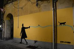 Elegant Men paints graffiti on a wall, followed by a black cat, By Italian graffiti artist kenny Random.