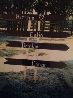 Hand cut and painted rustic pallet sign points guests in the right direction to wedding and reception areas