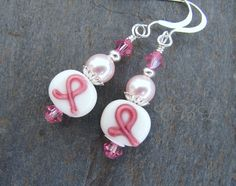 "Think Pink!  Pretty pink ribbon lampwork glass earrings created in remembrance of those lost to cancer, currently fighting cancer and the cancer survivors!  These earrings are teamed with Rose pink Swarovski Crystals, Rosaline (light pink) Swarovski Pearls, silver plated beads and bead caps and are completed with Sterling Silver earwires. These earrings will hang just over 1 1/2"".  20% from the sale of these earrings will go to the American Breast Cancer Foundation for research. Their…"