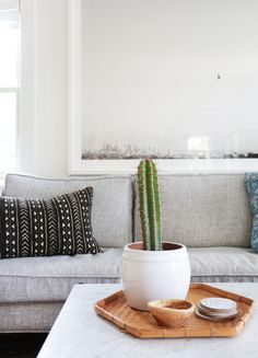 Mudcloth pillow, cactus, woven tray. Comfortable and cozy living space.