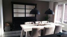 Landelijke keuken met zwarte buffetkast witte tafel en golden sun lampen