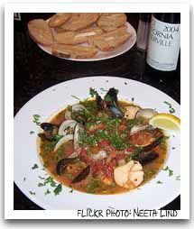 Cioppino  2 c. diced onion   6 cloves garlic, chopped   1/2 c. extra virgin olive oil   1 (35oz) can tomatoes   1 (6 oz) can tomato paste   2 c. dry red wine   1 lemon, sliced thinly   1 c. chopped fresh parsley, divided   1 tsp each dried oregano and basil   1 tsp salt   fresh pepper   1 1/2 lbs sea bass, deboned, chunked   3 lobsters cleaned, meat chopped   1 lb shelled shrimp   12 clams, cleaned   24 mussels, cleaned