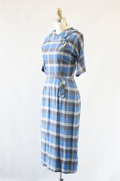 MAD FOR PLAID Cute plaid dress with saucy wiggle silhouette. FEATURES: • shirtwaist dress • bold plaid pattern • crossover shawl collar with decorative buttons • decorative tab on waist • long back zip • unlined  ERA: 1950s  LABEL: n/a  SIZE: small, about a 4 to 6 shoulder: 16 bust: 34 waist: 26 hips: 38 length: 43 pinned on model: no FABRIC: unmarked, super soft texture feels like cotton / acrylic blend. COLOR: blue and gray. CONDITION: excellent! no holes, stains, or discoloration...