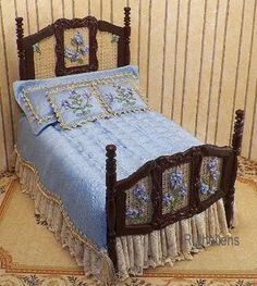 Handmade bed with cane inserts, fancy appliques, wood trim, stained mahogany. Embroidery work on the cane panels in blues and lavenders. French blue dupioni silk spread with tufted top and trimmed, scalloped sides. Single flanged pillow with two embroidered. Dust ruffle is fairy frost, tone on tone beiges and creams with lace trim.. Dramatic coloring for a master bedroom!