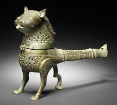 A Khorasan brass Incense Burner in the form of a lion  Persia, 12th Century the body on three legs with long handle terminating in palmette, the hinged lid in the form of a lion's head with extended tongue, engraved and decorated in openwork with interlaced vegetal motifs and a series of lozenge-shaped scale motifs along the lower side of the handle  30.5 cm. long