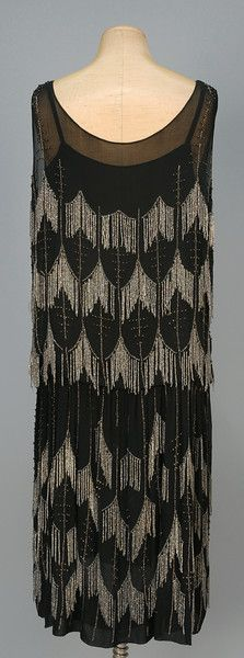DAIR PARIS CHIFFON FLAPPER DRESS with BEADED FRINGE, 1920s. Black silk with crystal fringe forming an allover scallop pattern with vertical bands of clear and silver beads, blouson top and chiffon underdress. Labeled.  Back