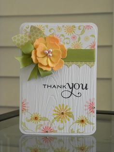 lovely handmade thank-you card ... sweet yellow felt flower ... die cut layers and slightly tinted at the edges ... white background with stamped flowers and wood grain embossing on it ...
