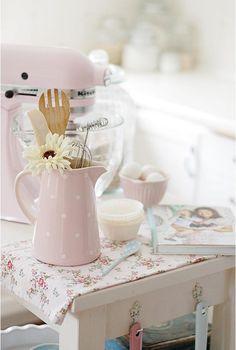Une jolie table rustique peinte en blanc, du tissu fleuri à petits motifs roses style Shabby, un pichet tout rose, des accessoires aux couleurs douces, contribuent à donner un air de campagne très jeune et très frais à cette cuisine.