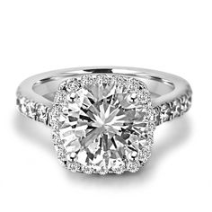 Get the best of both worlds with this gorgeous 18k white gold engagement ring showcasing a sparkly round-cut center diamond set in a dazzling cushion shaped halo. Dreams do come true!<br /> <br /> Pricing varies based on diamond weight and quality. Inquire below for specifications.