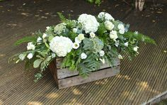 White roses, hydrangea, lisianthus against a backdrop of luxurious foliage with lots of texture for a loved one