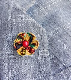 An African cotton lapel flower pin made in the Japanese tsumami kanzashi style! I used a colorful replica African kente cloth to make the flower, sewed a red coral bead into the center, and mounted everything on a tie tack finding. Complements a blazer, sport jacket, suit, suspenders, cardigan, overcoat, vest, or hat.  Kanzashi flowers are made from folded fabric squares, one petal at a time. Originally, apprentice geisha made kanzashi hair accessories from their old kimonos. DETAILS…